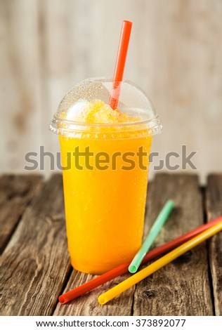 Still Life Profile of Refreshing and Cool Bright Orange Slush Drink in Plastic Cup with Lid Served on Rustic Wooden Table with Collection of Colorful Drinking Straws - stock photo