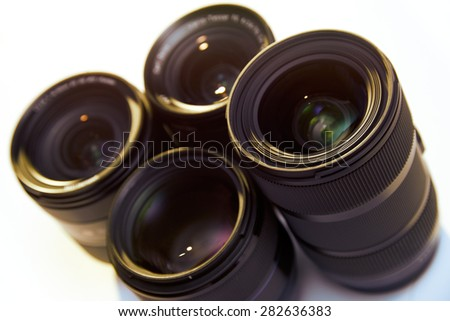 Still life shot of group of photographic lenses isolated on white background, with warm backlight and flare. High angle view - stock photo