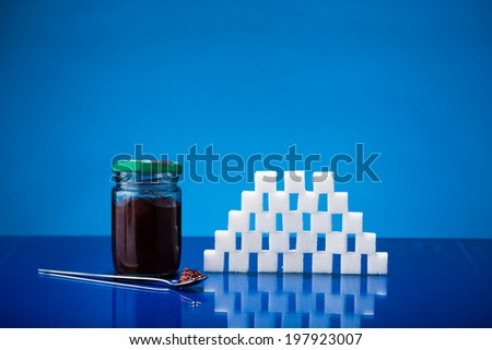 Still life showing amount of sugar in a jar of jam - stock photo