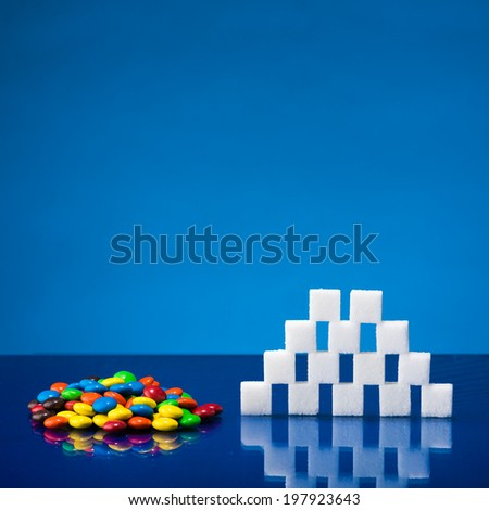 Still life showing amount of sugar in a portion of candies - stock photo