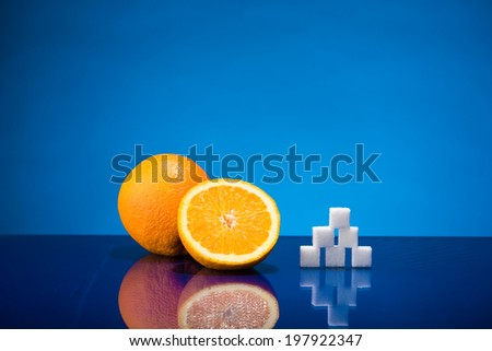 Still life showing amount of sugar in one and a half orange - stock photo