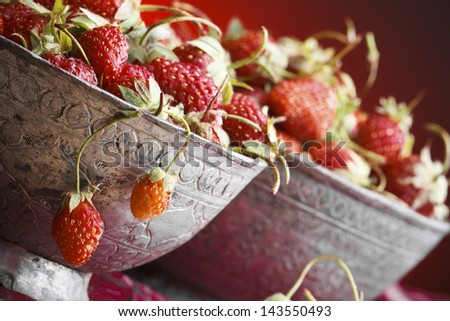 Still Life - Strawberries in Bowls Against Colored Background - stock photo