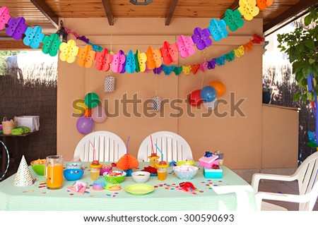 Still life view of a children birthday party table decorated with fun and colorful deco and balloons in a home garden space, outdoors. Kids party decorations and fun activities space, home exterior. - stock photo