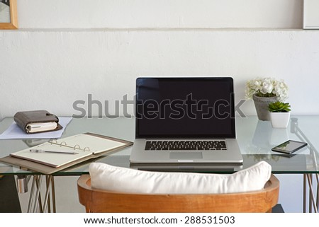 Still life view of a home office room with a laptop computer and a smart phone, house interior. Working from home technology in a home work desk, indoors. High technology lifestyle workplace. - stock photo