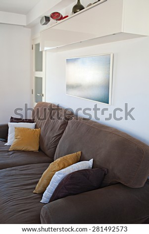 Still life view of an apartment living room with a sofa and cushions in a bright home interior. Comfortable family living room with a picture frame on the wall, house interior and home living detail. - stock photo