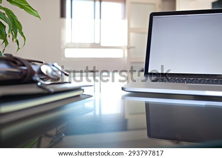 Still life view of an office room with an open laptop computer on a glass desk with reflections window, office interior with paperwork and chair. Slick and professional workplace, technology indoors. - stock photo