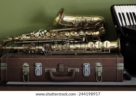 Still life vintage music  on musical instruments with saxophones and accordion background  - stock photo