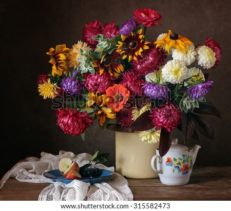 Still life with a beautiful bouquet of country flowers, apple and a retroteapot. - stock photo