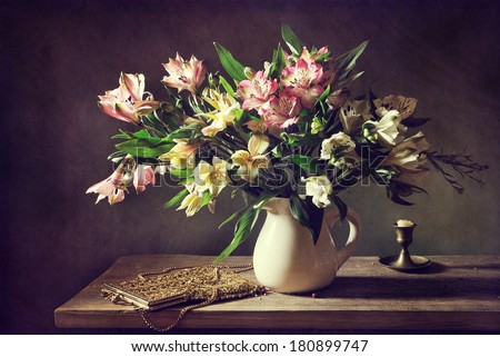 Still life with a beautiful bouquet of flowers and a vintage bag - stock photo