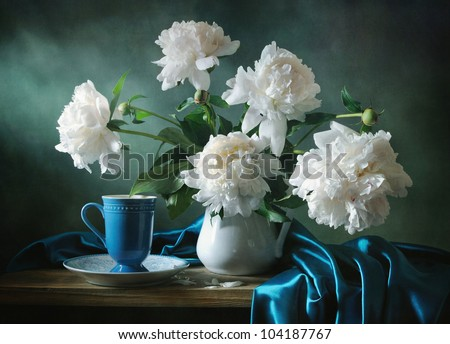 Still life with a blue cup and a bunch of peonies - stock photo