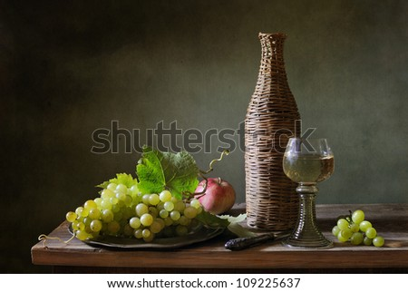 Still life with a bottle of wine and grapes - stock photo