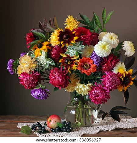 Still life with a bouquet of autumn flowers, apple and berries - stock photo