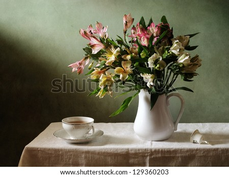 Still life with a bouquet of flowers and a cup of tea - stock photo