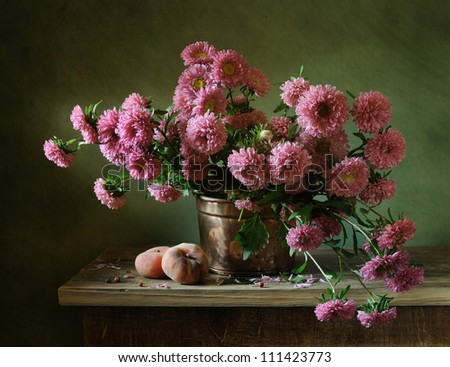 Still life with a bunch of asters and peaches - stock photo