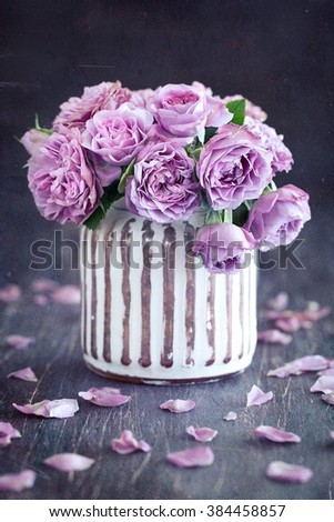 Still life with a fresh purple roses in a vase on a dark brown wooden background . - stock photo