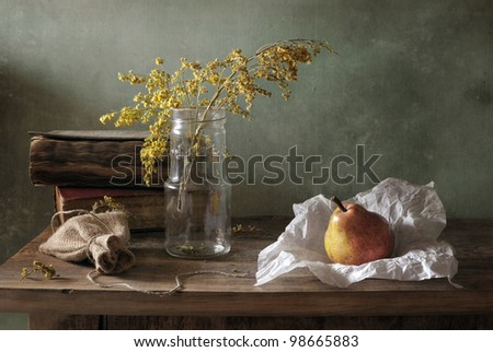 Still life with a glass bottle and a pear - stock photo