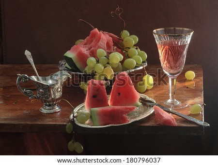 Still-life with a juicy red water-melon both juicy green grapes and pink wine, fresh appetizing juicy sweet fruit in an unusual copper vase and fragrant pink wine in a graceful crystal glass fruit  - stock photo