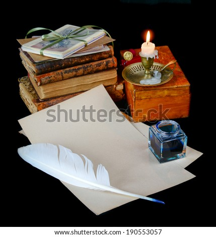 Still life with a letter, a pen, a lighted candle in copper candlestick and a pile of old books on a dark background - stock photo