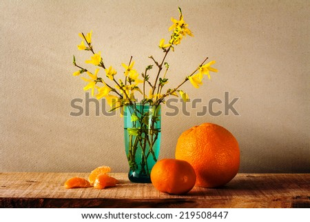 Still life with a spring bouquet of yellow forsythia and oranges - stock photo