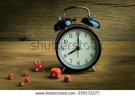 Still life with alarm clock and red dices on the wooden table - stock photo