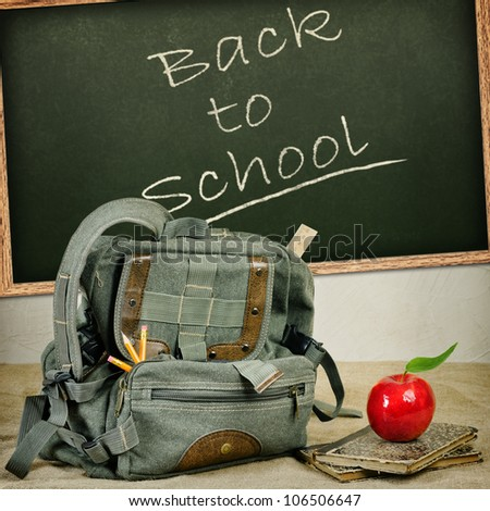Still life with an old backpack, books and red apple - stock photo