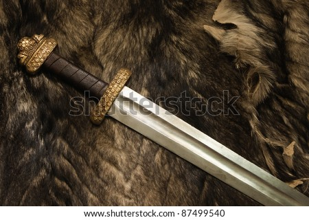 Still life with ancient scandinavian sword on a fur - stock photo