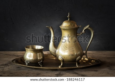 Still life with antique teapot on wooden table - stock photo