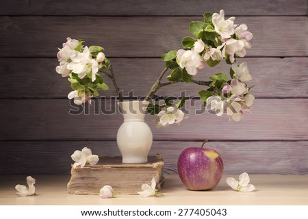 Still life with apple, old book and blossoming branch - stock photo