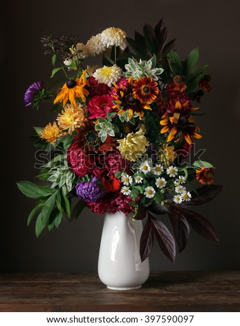 Still life with asters and chrysanthemums in a white jug on a dark background. - stock photo