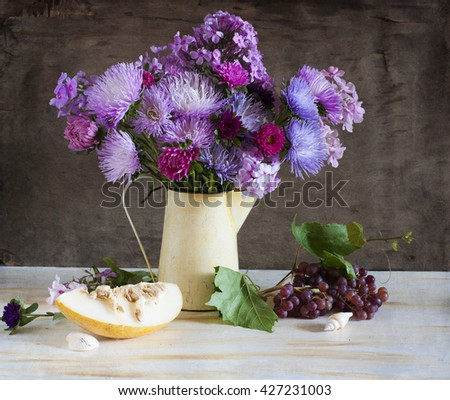Still life with asters and melon - stock photo