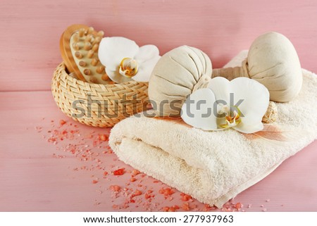 Still life with beautiful blooming orchid flower, spa treatment and pebbles, on color wooden background - stock photo