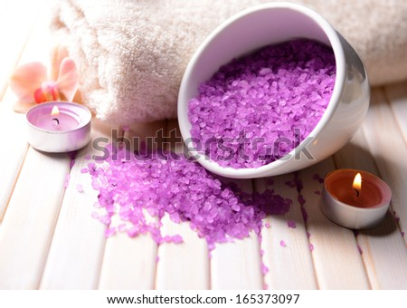 Still life with beautiful blooming orchid flower, towel and bowl with sea salt, on color wooden background - stock photo