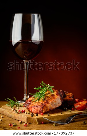 still life with beef steak, rosemary and glass of red wine - stock photo