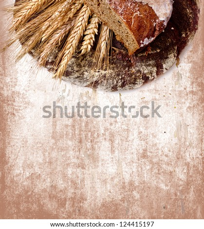 still life with black bread and ears of wheat/composition with natural fresh bread and ears of rye on a vintage background/diet of brown bread/healthy eating - stock photo