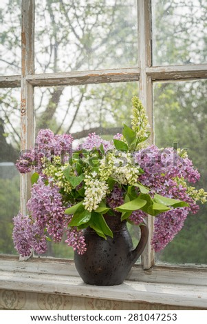 Still life with blooming branch of lilac on a window sill - stock photo
