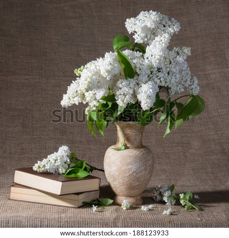 Still life with  blooming branches of lilac in vase and books - stock photo
