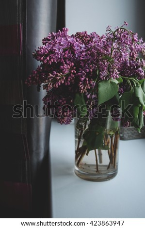 Still life with blooming spring branches of lilac flowers in vase, dark background. Home decoration in a rustic style. Violet bouquet on white windowsill in room. - stock photo