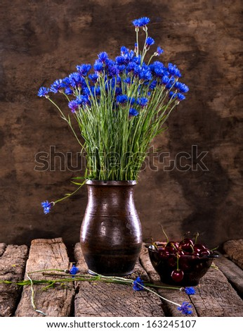 Still life with  blue cornflowers in vase and cherries on a wooden background - stock photo