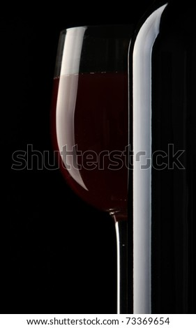 Still-life with bottle and footed glass - stock photo