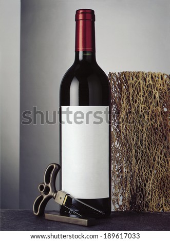 Still life with bottle of red wine and cork screw - stock photo