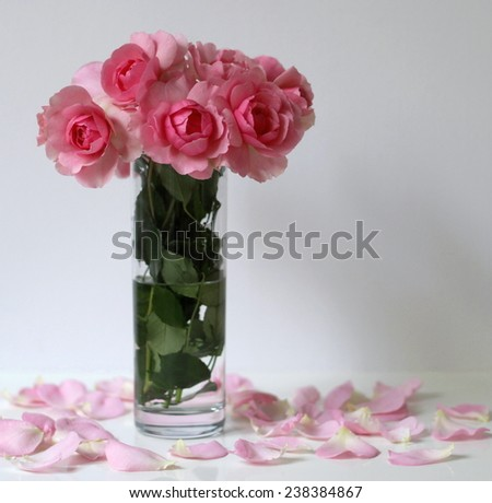 Still life with bouquet of pink roses in a glass vase and petals. Romantic floral decoration. - stock photo