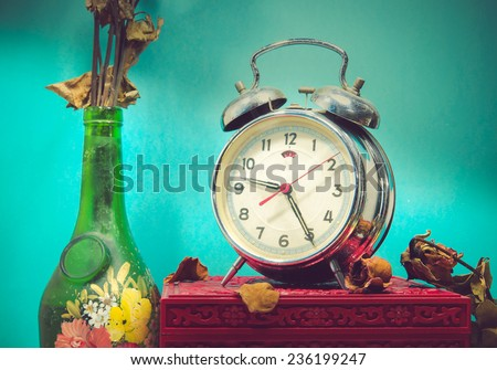 Still life with broken alarm clock, old glass vase with dead rose, vintage box, tone image. - stock photo