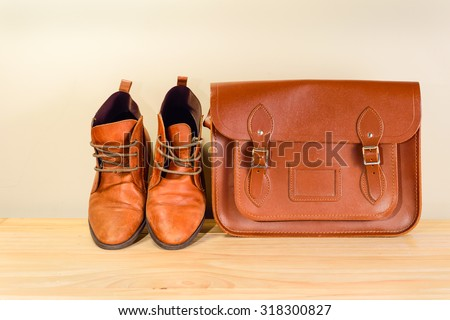 Still life with Brown leather shoes with leather bag on wooden table - stock photo