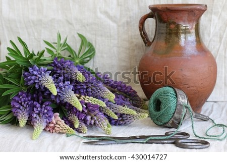 Still life with bunch, bouquet  blue flowers of lupines, very old clay brown pitcher, industrial funnel, holder for green sisal twine, vintage scissors, grey natural linen background  - stock photo