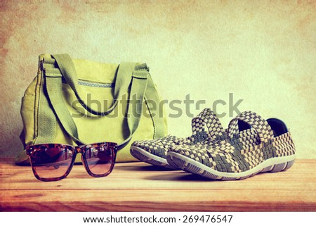 Still life with casual woman, shoes, sunglasses, and bag on wooden table over wall background - stock photo