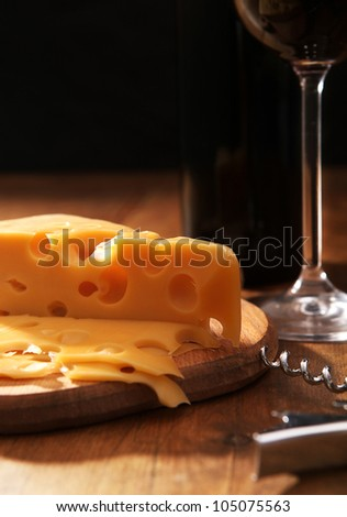 Still life with cheese and wine in contrasting light - stock photo