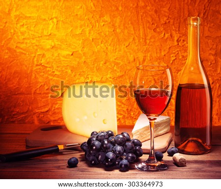 Still-life with cheese, grapes and glass and bottle of red wine.Filtered image: vintage effect. - stock photo