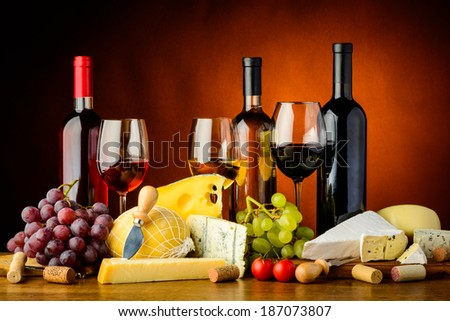 still life with cheese, grapes, red, white and rose wine - stock photo