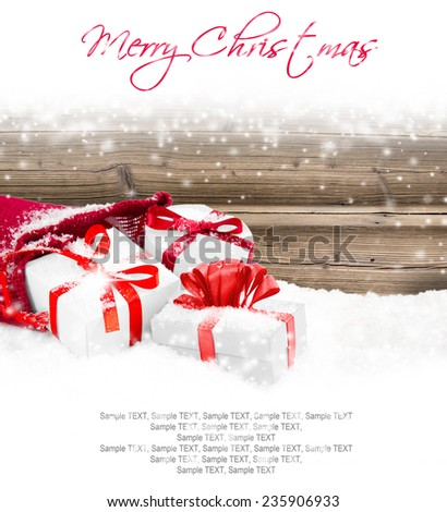 Still life with Christmas bag full of gifts on wooden board covered with snow - stock photo