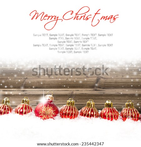 Still life with Christmas balls on wooden board covered with snow - stock photo